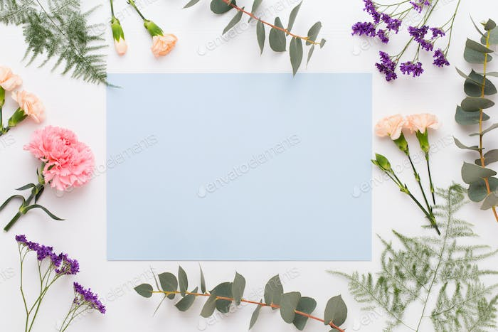 Paper blank, flowers, eucalyptus branches on pastel  background.