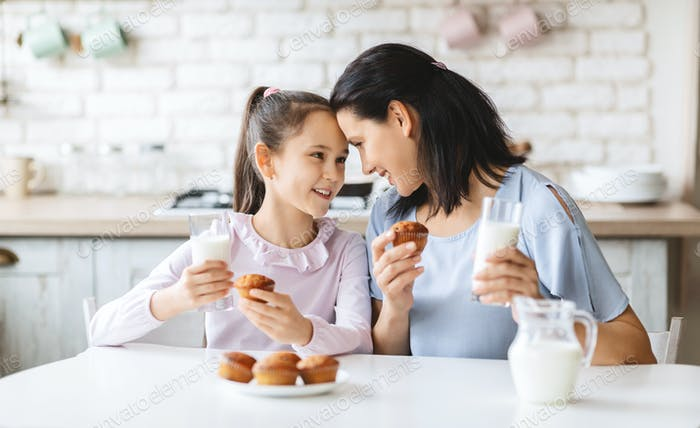 Mother and daughter having a bite in kitchen