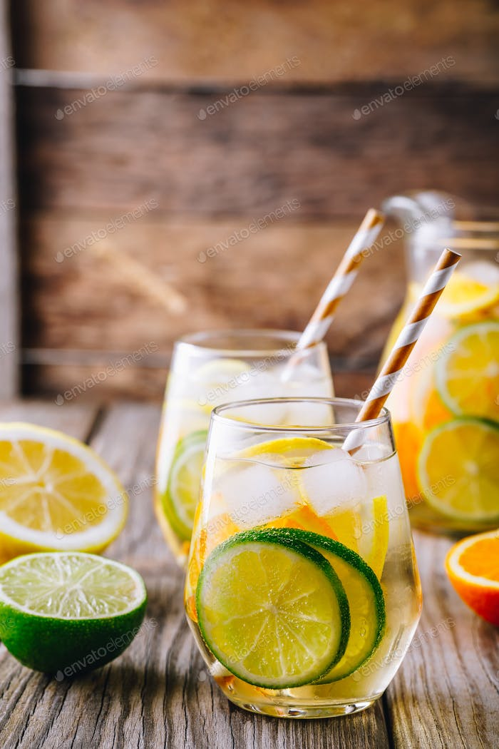 A refreshing summer ice-cold drink. White wine sangria in glass with lime, lemon and orange