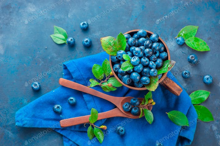 Blueberries in a ceramic cup with wooden spoons and a linen napkin. Ripe and sweet summer berries on