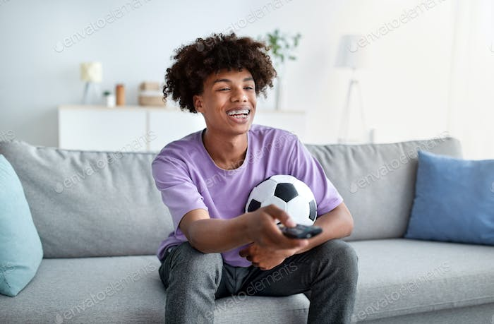 Happy black teenager watching football game on TV at home