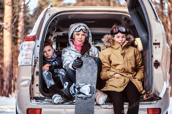 A beautiful woman and her sons dressed in warm clothes sitting on the trunk of a car