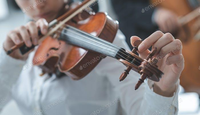 Violinist tuning a violin