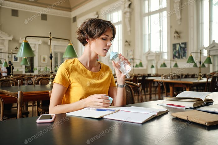 Young attractive casual female student drinking water during study in library of university