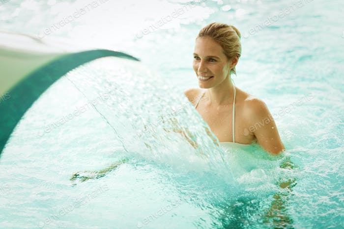 Beautiful woman enjoying jet of water in wellness resort