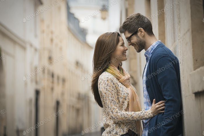 A couple standing gazing at each other, in a narrow street in a city.