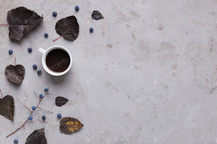 Espresso coffee with dark fallen leaves on gray background