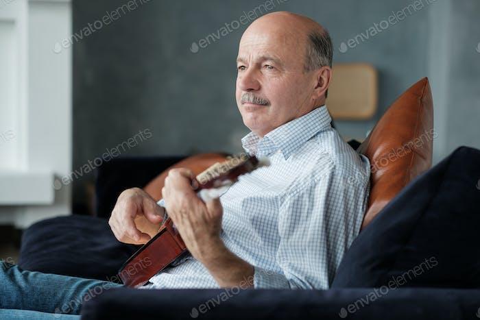 Senior man playing acoustic guitar at home