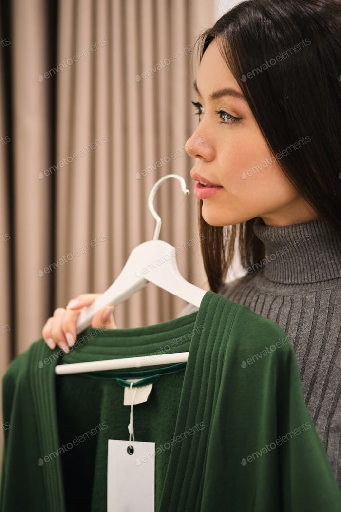 Portrait of beautiful stylish Asian girl thoughtfully trying on cardigan in fashion store