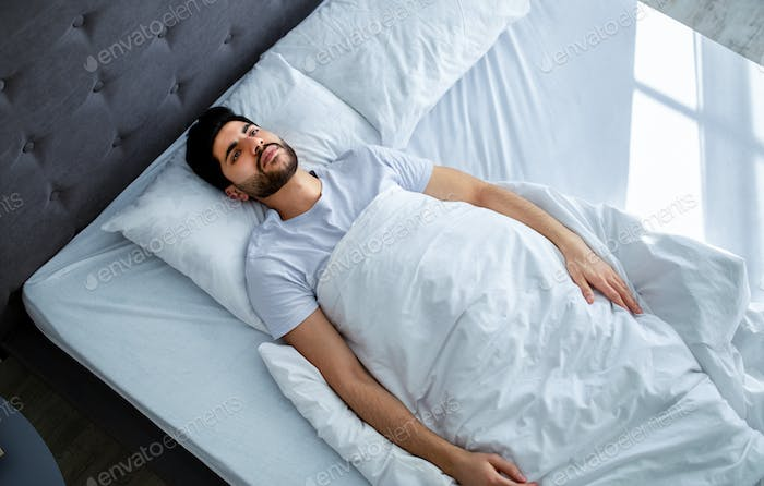 Unhappy arab man having insomnia unable to sleep, lying in bed, looking up and contemplating, copy