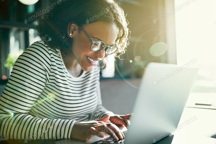 Young African woman smiling and using a laptop