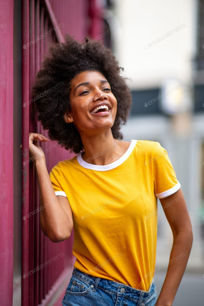 happy beautiful young black woman with afro hair outside