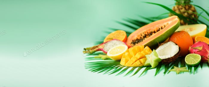 Assortment of exotic fruits on turquoise background. Banner. Detox, vegan food, summer concept