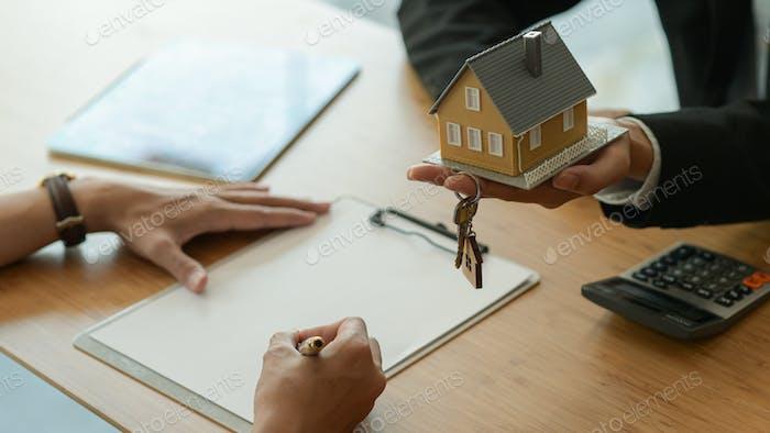 Hausmakler stellt den Kunden vor, den Kaufvertrag zu unterzeichnen.
