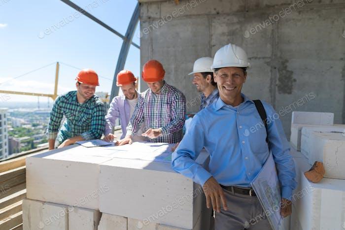 Erfolgreicher Geschäftsmann über Team von Bauherren diskutieren Blueprint Plan nach dem Treffen der Ingenieure