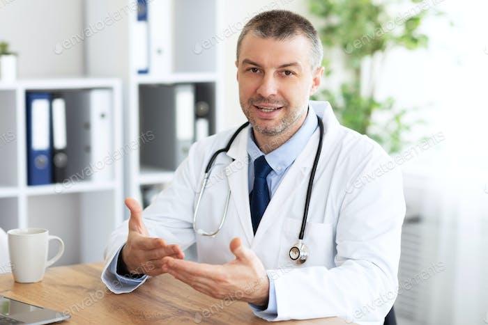 Portrait of senior doctor consulting his client, patient's pov