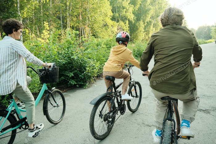 Active family of husband, wife and their son of elementary age riding bicycles