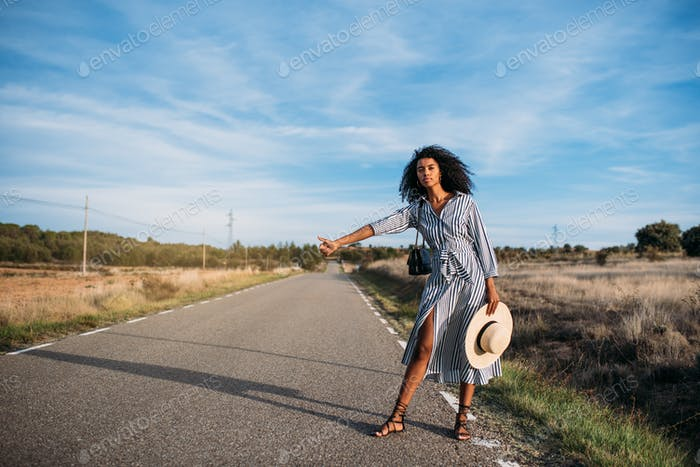 Happy black woman hitchhiking with thumbs up