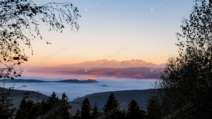 Landscape view of Spis castle and High Tatras mountains at sunri