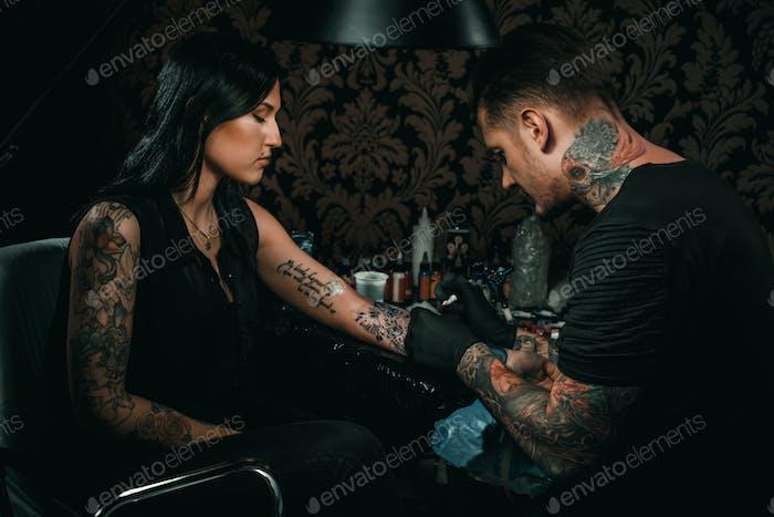 Профессиональный татуировщик делает татуировку на руке молодой девушки