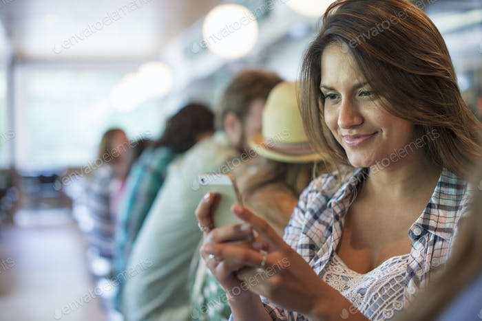 A woman in a diner, looking at her cell phone.