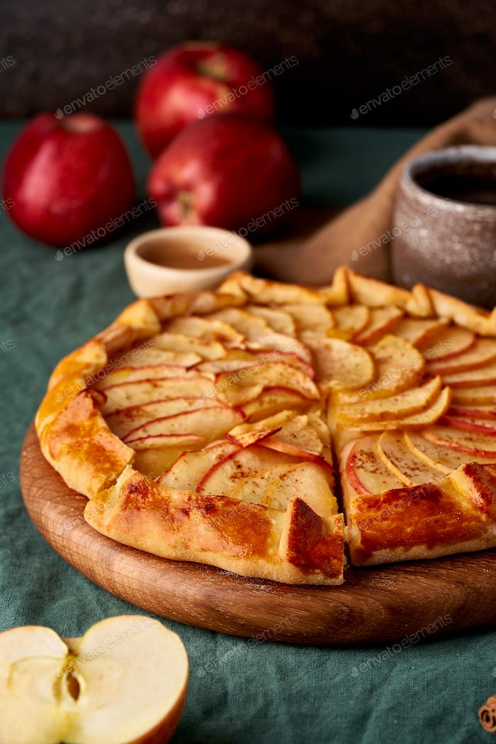 Apple pie, galette with fruits, sweet pastries on dark green tablecloth, vertical