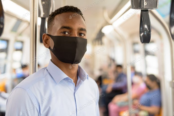 Young African businessman with mask for protection from corona virus outbreak standing with distance