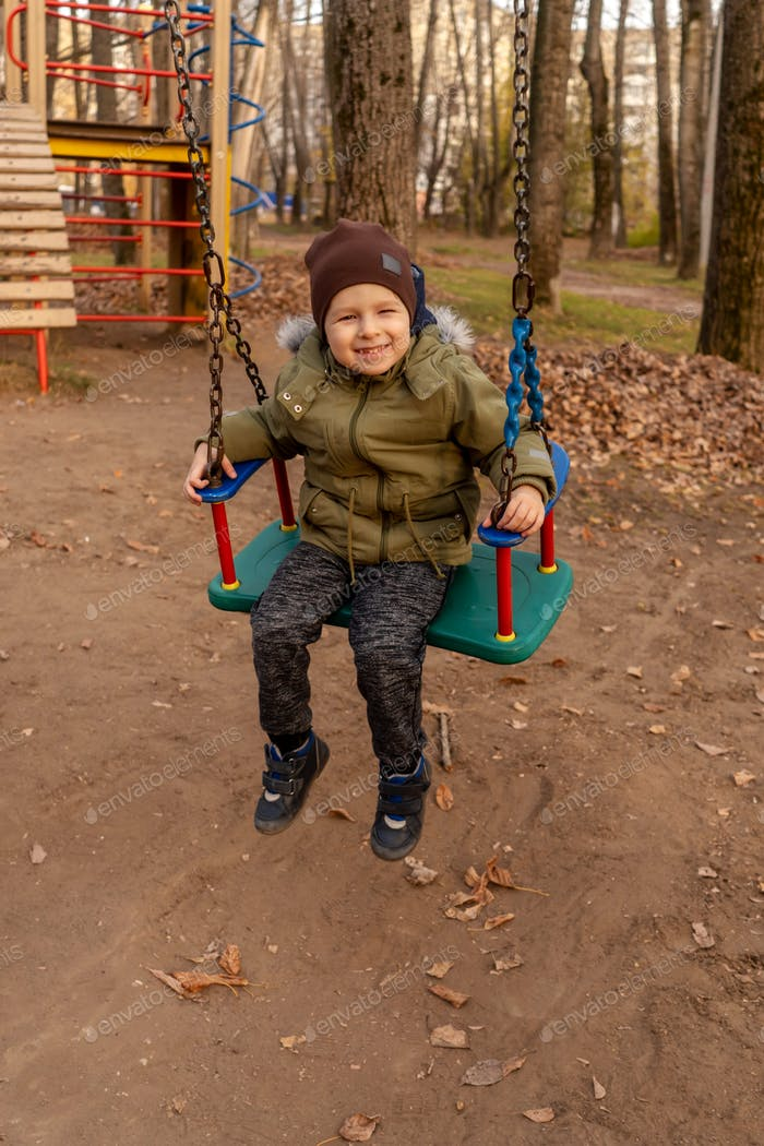 Young toddler boy swinging on a swing