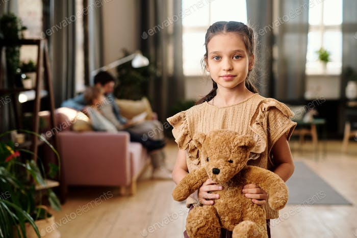 Cute girl with teddybear standing in living-room