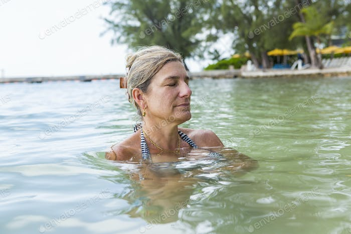adult 40's woman relaxing in ocean water, Grand Cayman Island
