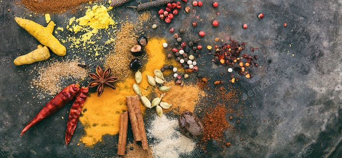 Variety of colorful spices on metal rusty background, top view, copy space, banner