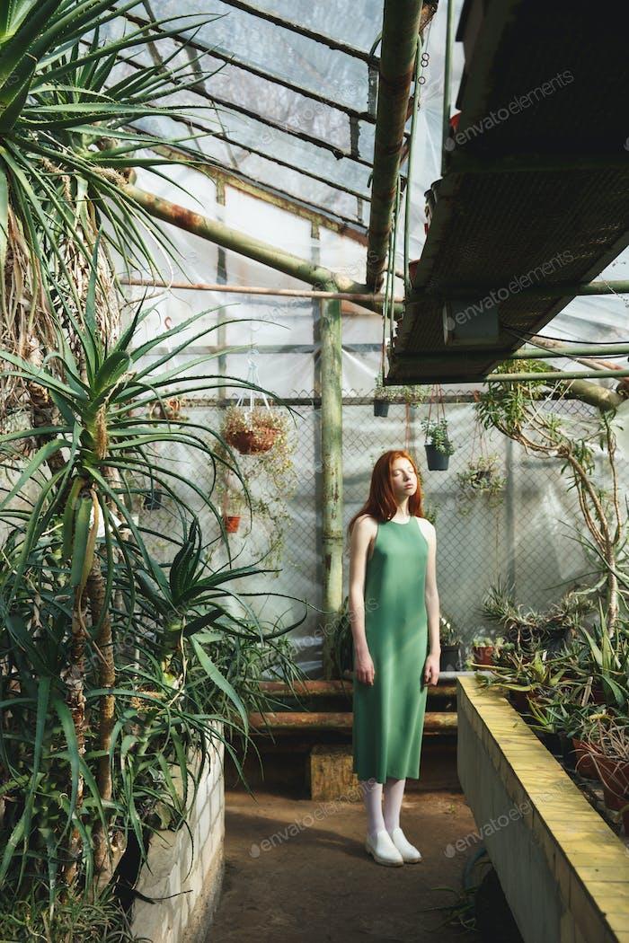 Full-length shot of beautiful girl standing in greenery