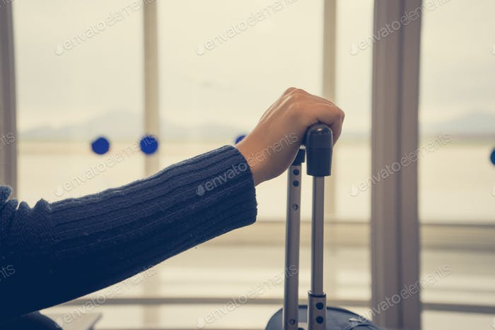 Girl holding suitcase in the airport