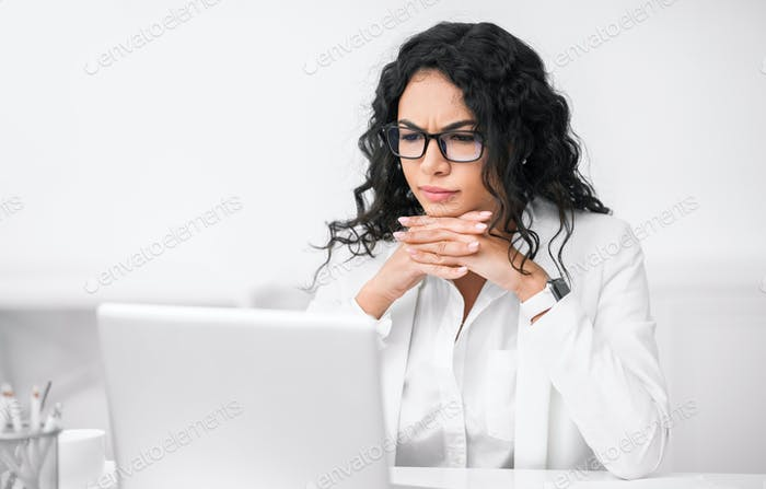 Serious hispanic manager using her personal computer