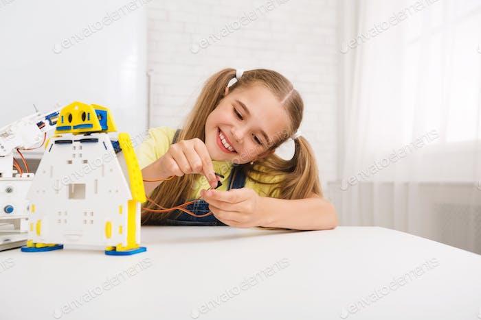 Robot details. Nice girl constructing diy robot