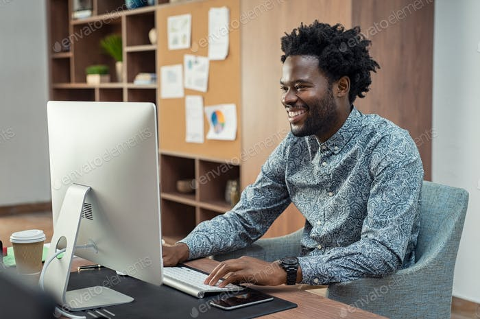 Happy african businessman using computer