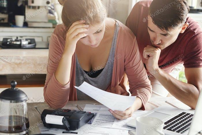 Junges Paar berechnet sein inländisches Budget zusammen in der Küche und versucht, Geld für den Kauf zu sparen