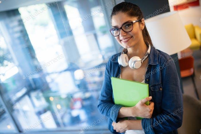Schöne glückliche Student Frau studieren in Bibliothek