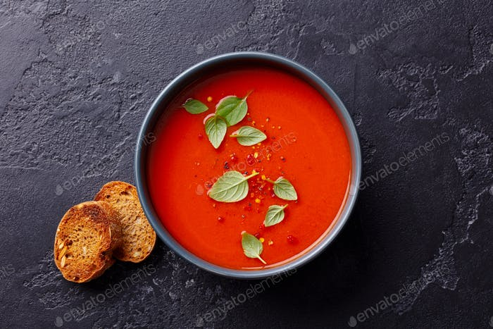 Tomato Soup with Basil in a Bowl. Dark Background. Top View.