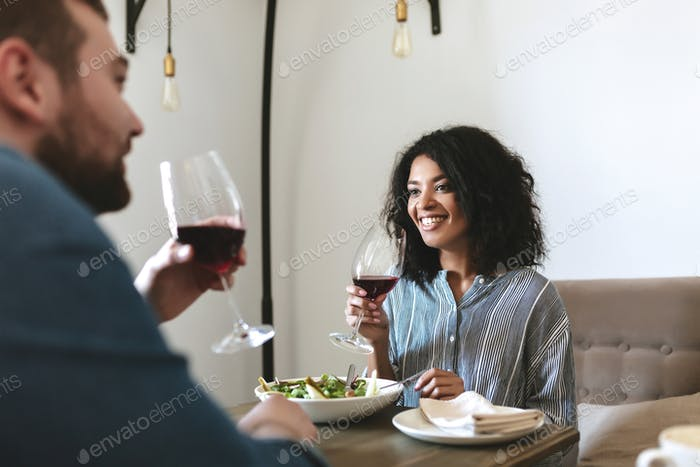 Beautiful African American girl eating salad and drinking wine at cafe