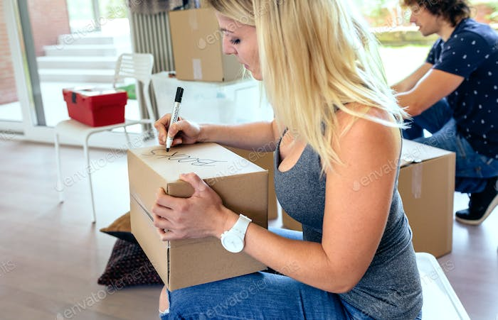Sitting woman labeling moving boxes