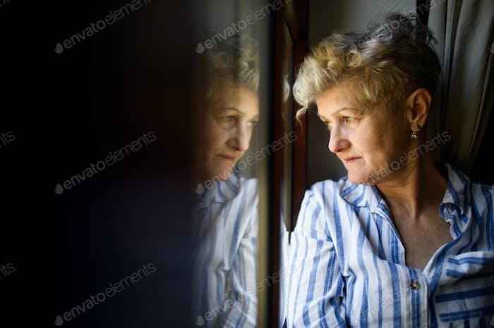 Sad senior woman standing indoors at home, corona virus and quarantine concept