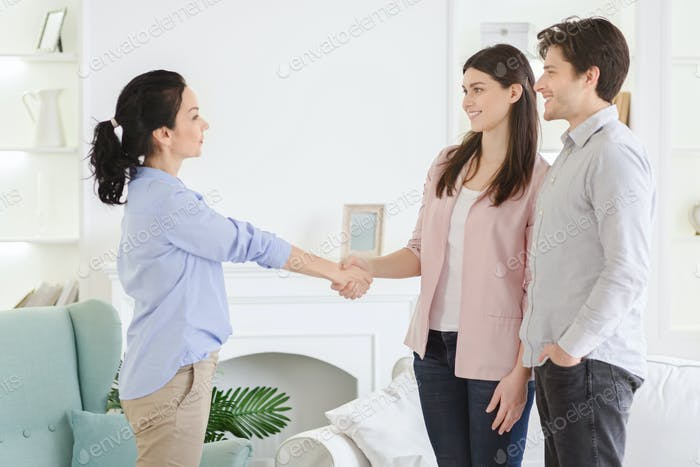 Professional psychologist and thankful couple handshaking in office