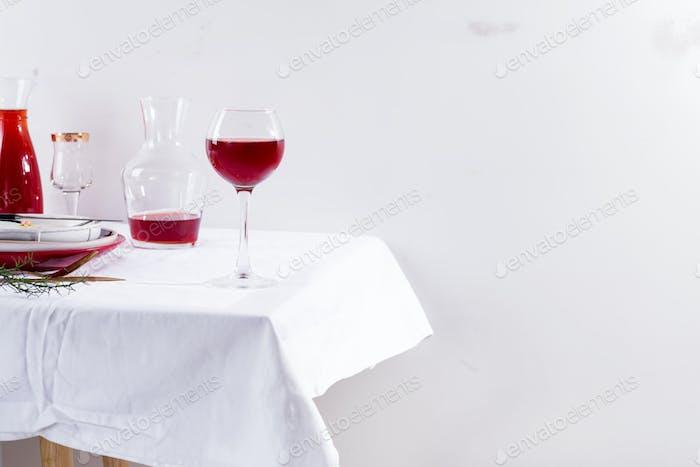 Rotwein im Weinglas, Dekanter und Flasche mit Schatten isoliert auf weißem Textilhintergrund