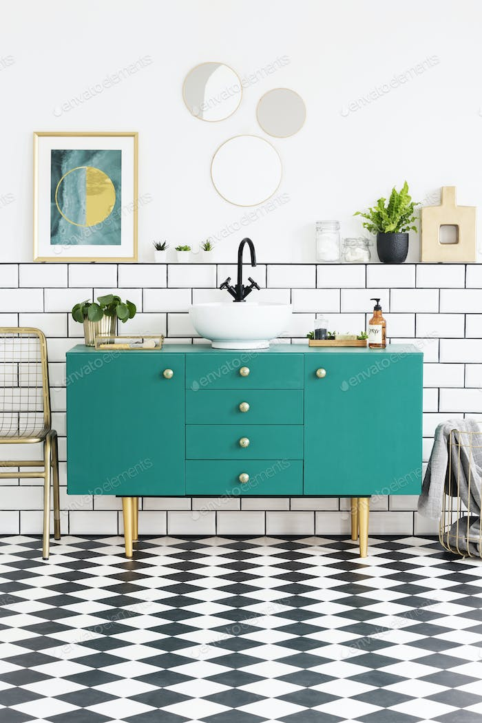 Mirrors and poster above green cabinet in bathroom interior with