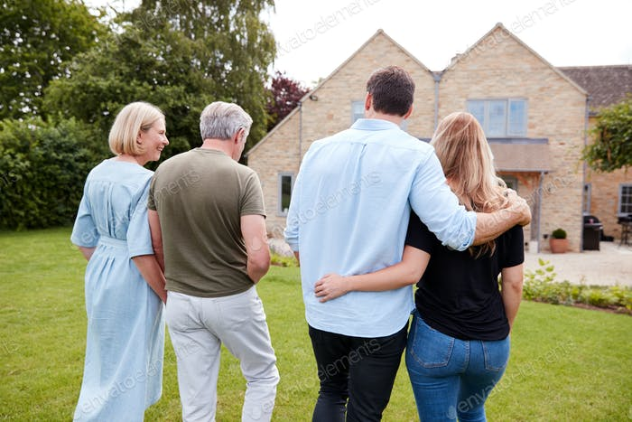 Rear View Of Family With Senior Parents And Adult Offspring Walking And Talking In Garden Together