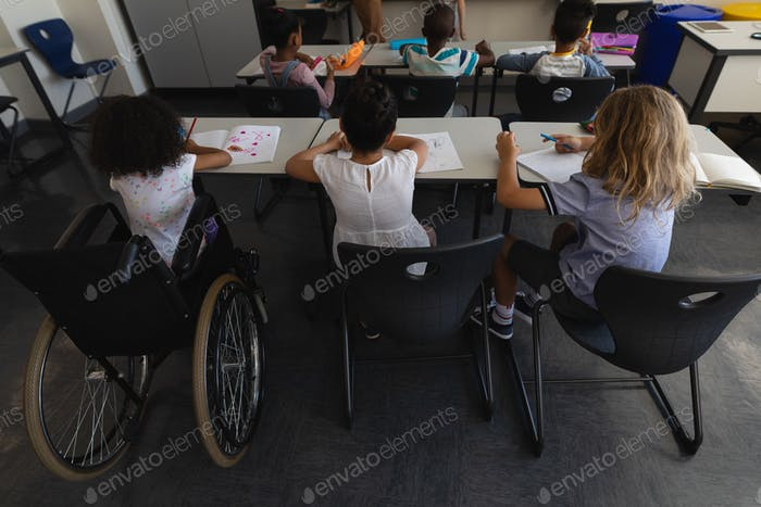 High angle view of disable schoolgirl with classmates studying and sitting at desk in classroom