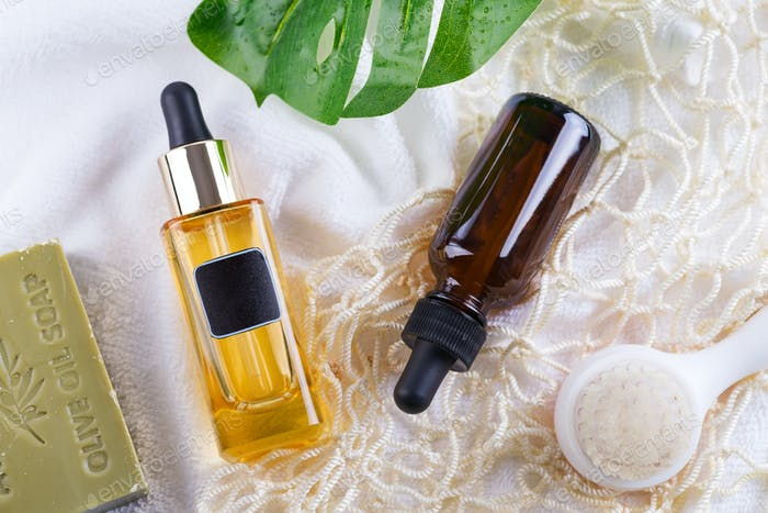 Cosmetic bottle with serum and hyaluronic acid , palm leaf, olive soap and Reusable shopping bags on
