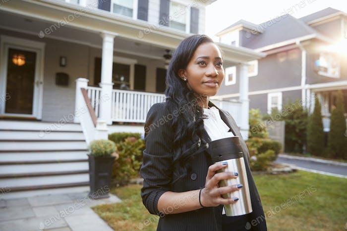 Geschäftsfrau mit Tasse Kaffee verlassen Suburban Haus für die Arbeit