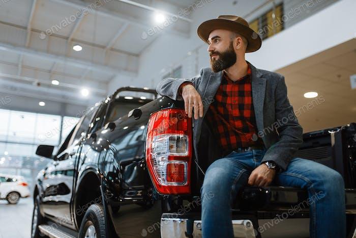 Man in hat poses at pickup truck in car dealership